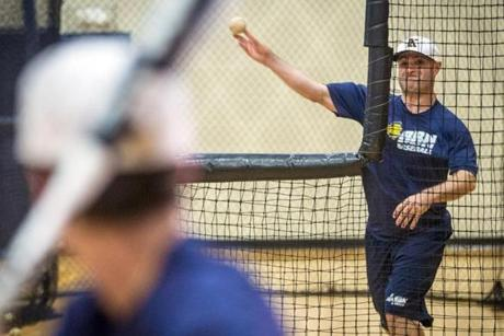 Eddie Tribble, assistant coach, pitched in the batting cage at Buckingham Browne & Nichols in Cambridge. He maintains an active lifestyle regardless of his blindness.
